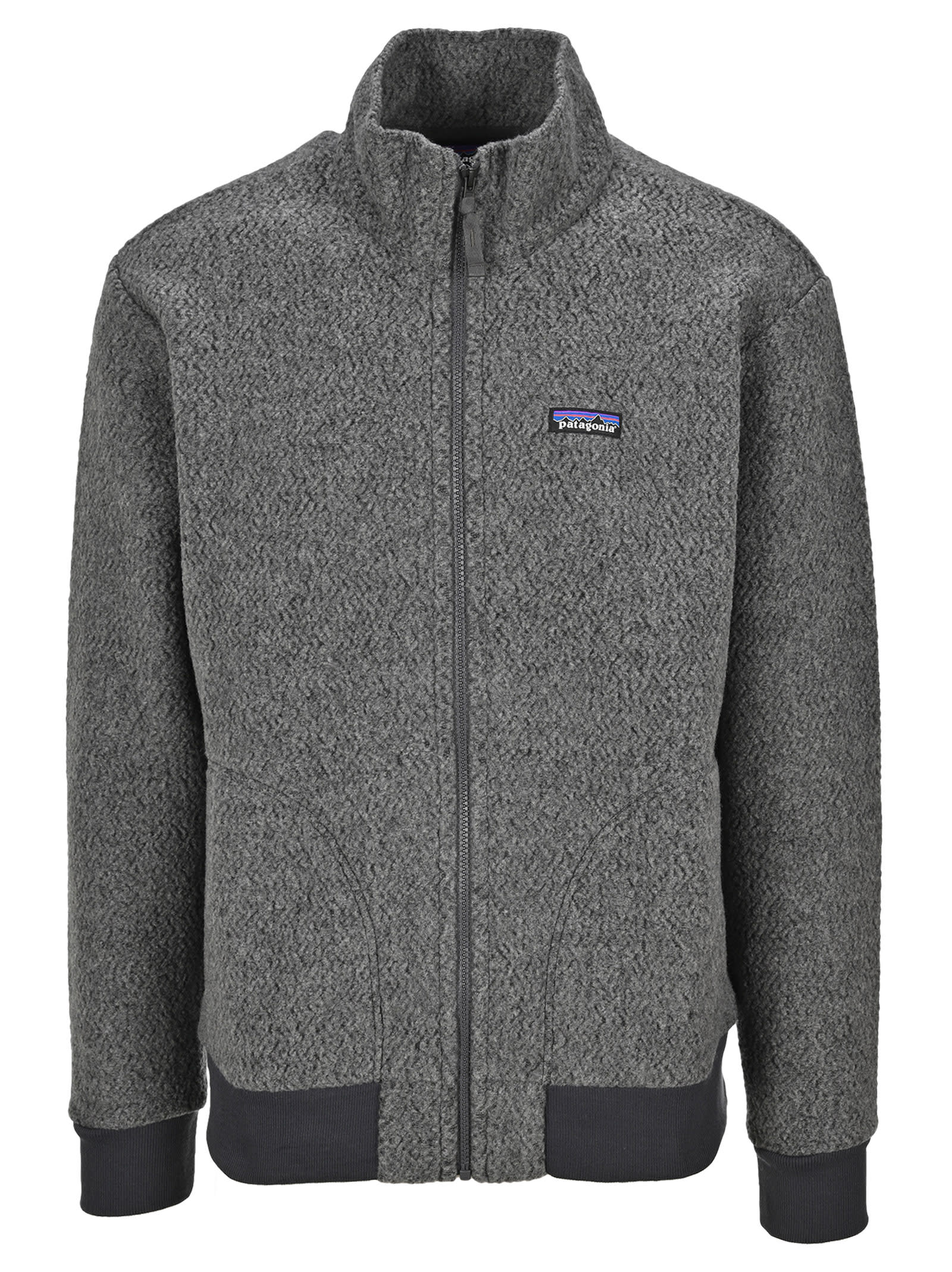 Woolyester Fleece Rib-trimmed Jacket By Patagonia. Featuring: - High Neck; - Front Zip Fastening; - Logo Patch At The Chest; - Side Pockets; - Long Sleeves; - Ribbed Hem And Cuffs. Composition: 46% POLYESTER, 46% RECYCLED WOOL, 4% NYLON, 4% OTHER FIBER