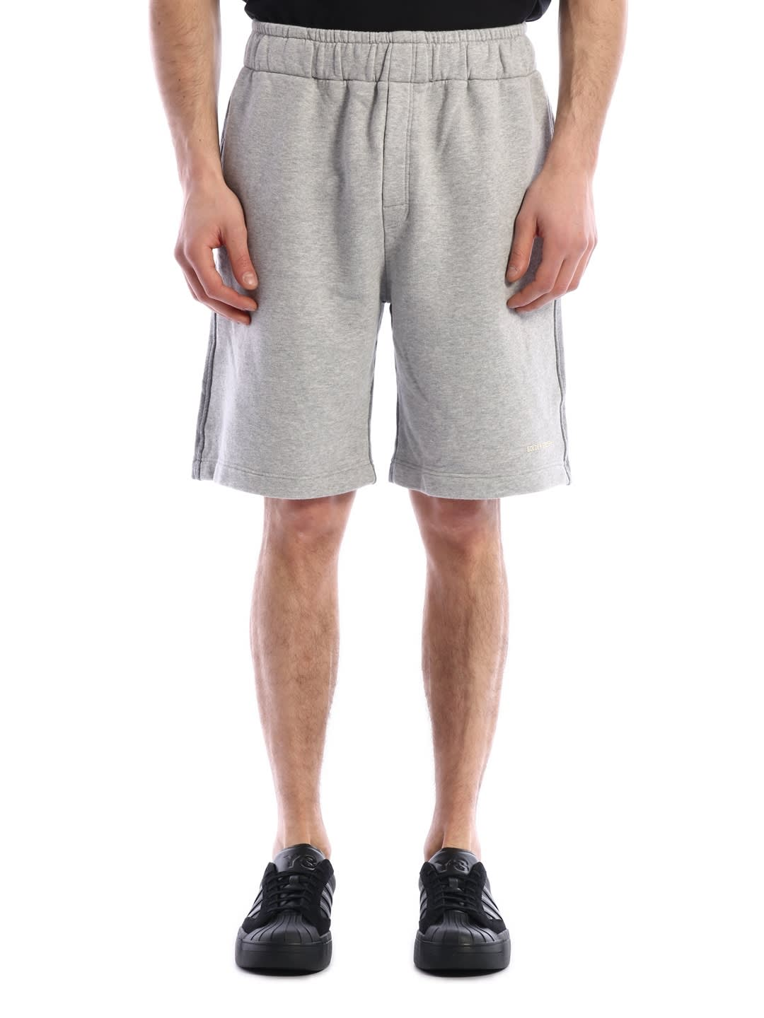 Grey cotton shorts featuring an elasticated waistband, side pockets, a rear pocket and a relaxed fit. The model is 183 tall and wears size MComposition: 100% Cotton